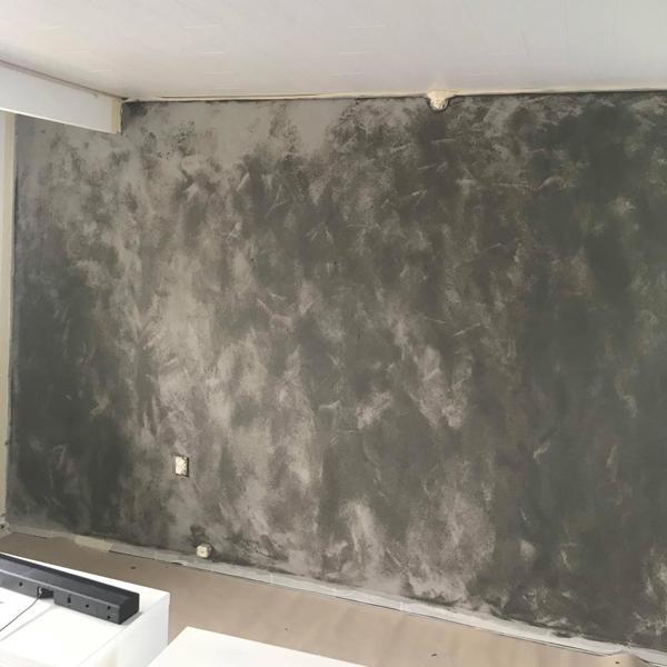 Væggen bliver langsomt lysere, som malingen tørrer.
